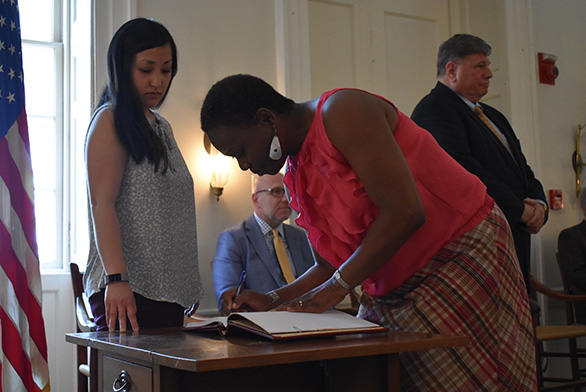 Graduate Institute student Tanya Fuller signs the College Register during Convocation.