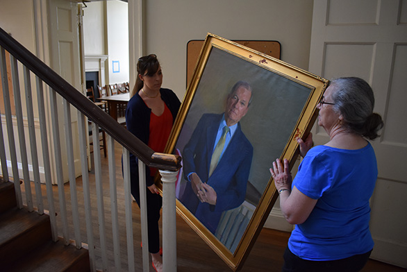 Two women move a painting in McDowell Hall