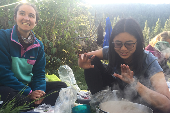 Freshmen Erin Luthin, left, and Bridget Wu smile over a steaming pot.