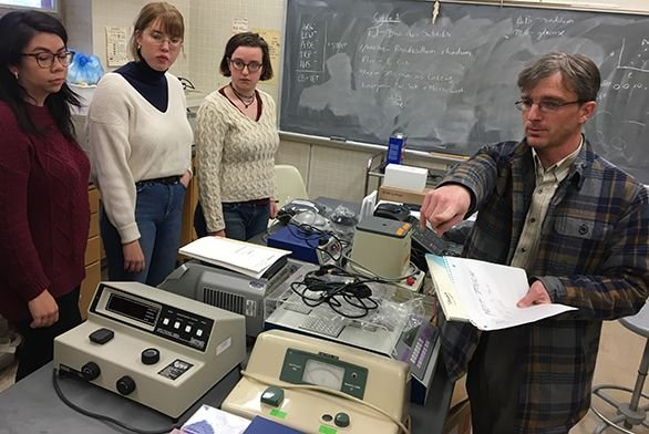Tutors Llyd Wells discusses lab equipment with students.