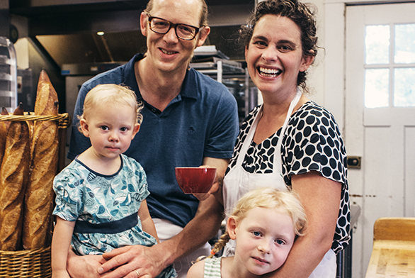 Chris Simmons and Lucy Montgomery share a family moment with their two daughters in their shop's kitchen.
